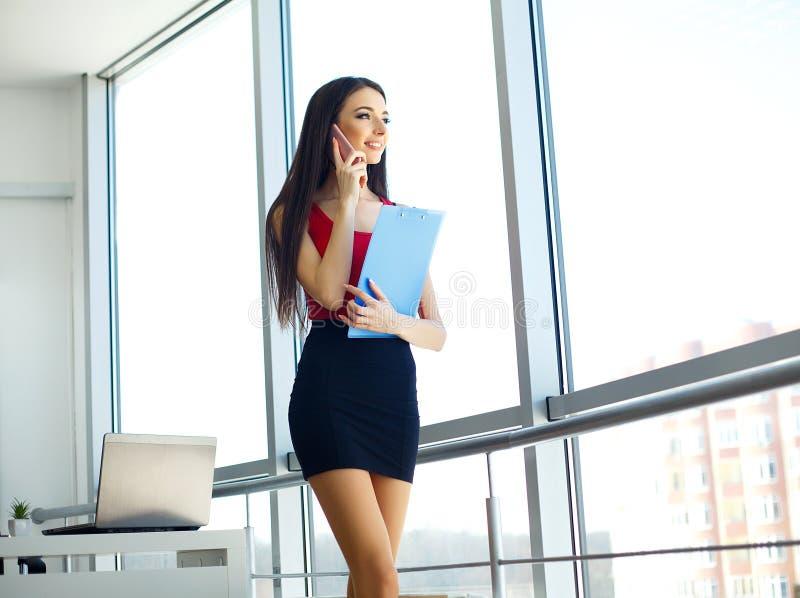 officemates Biznesowej kobiety pozycja przy Uroczystym okno Lekki Nowożytny biuro Ubierający w Czerwonym pulowerze i czerni spódn obraz royalty free