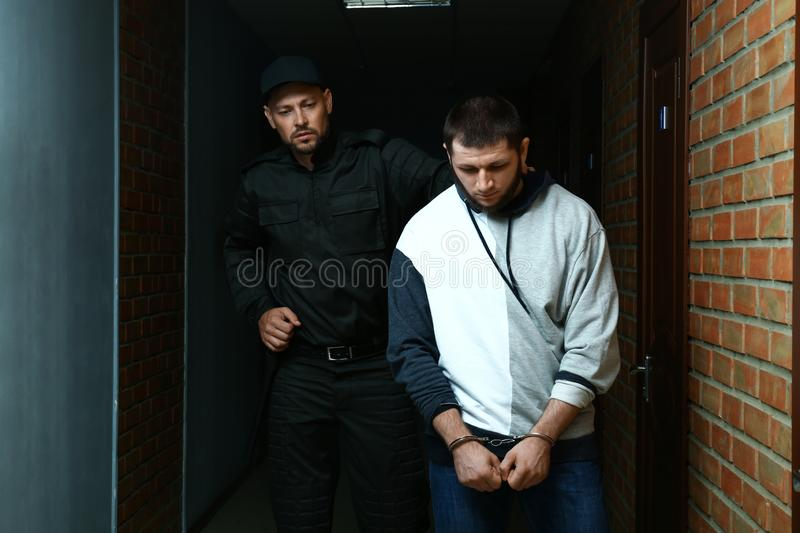 Officer with baton escorting criminal in police. Station stock photos