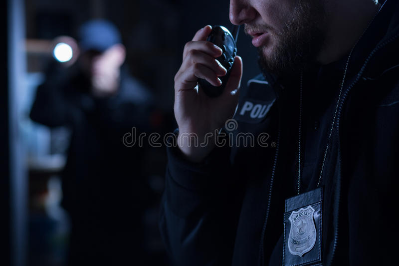 Officer using walkie talkie. During police intervention stock photography