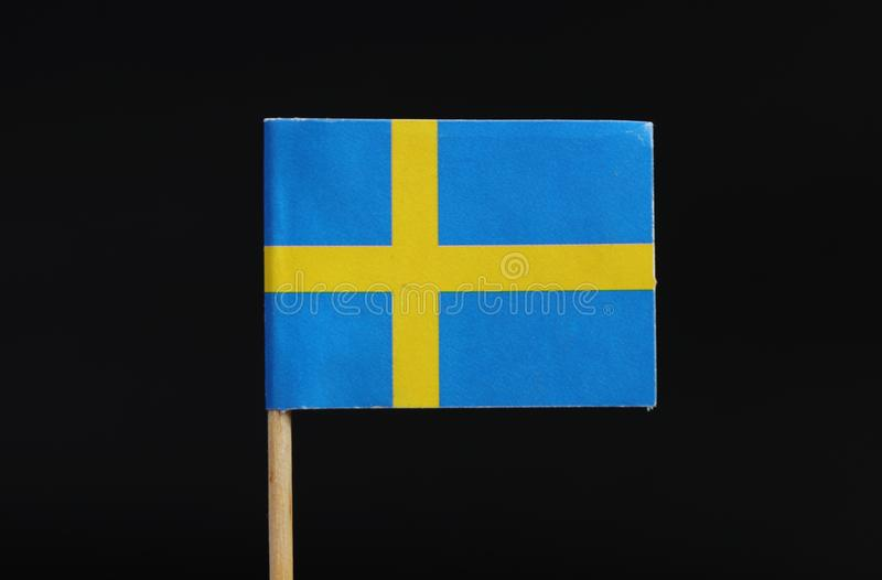 A official flag of Sweden on toothpick on black background. A blue field charged with a yellow Nordic cross that extends to the. Edges; the vertical part of the royalty free stock photography