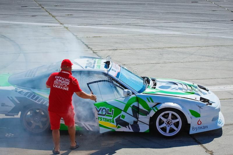 Official judge opens a door of a Nissan Silvia drift car to ventilate inside it and tell the result to driver, Vinnytsia Drift Com royalty free stock photography