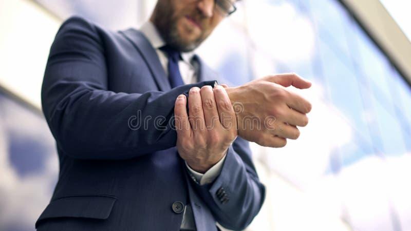 Official male feeling wrist pain, inflammation discomfort, osteoarthritis sprain. Stock photo stock images