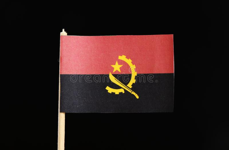 A official and national flag of Angola on toothpick on black background. Two horizontal bands of red and black with the Machete an stock images
