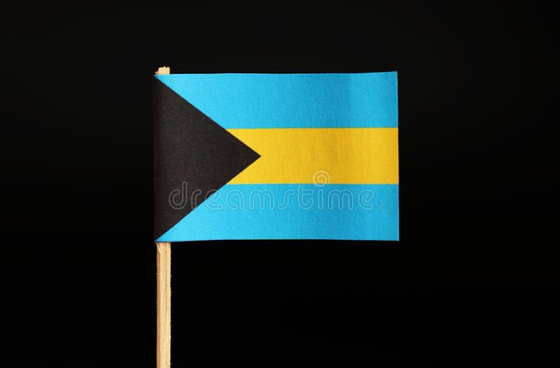 A official national Flag of the Bahamas on wooden stick on black background. The state located on north america. It was colony of united kingdom stock photo