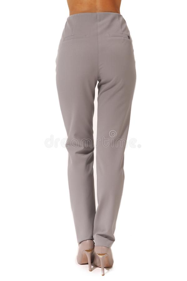 Official trousers on model legs with white stiletto heels. With bare toes stock image