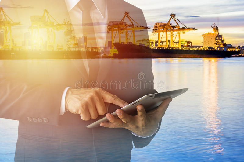 Officials are working on a tablet. Checking out a large industrial factory, wearing a black suit. White shirt, black tie royalty free stock image
