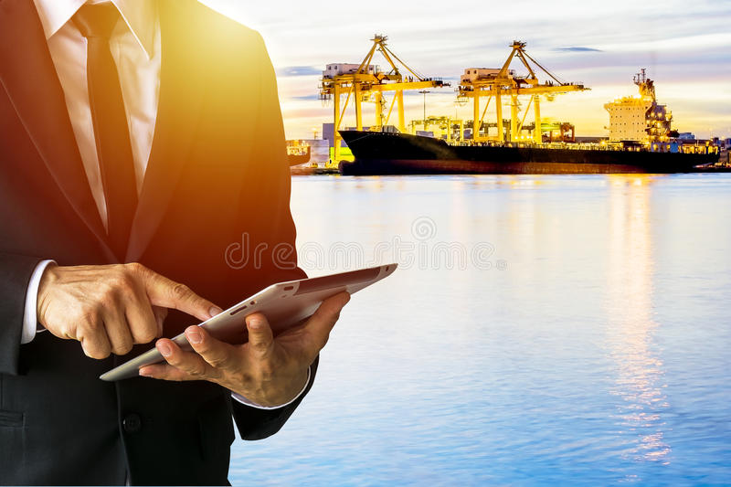 Officials are working on a tablet. Checking out a large industrial factory, wearing a black suit. White shirt, black tie stock photos