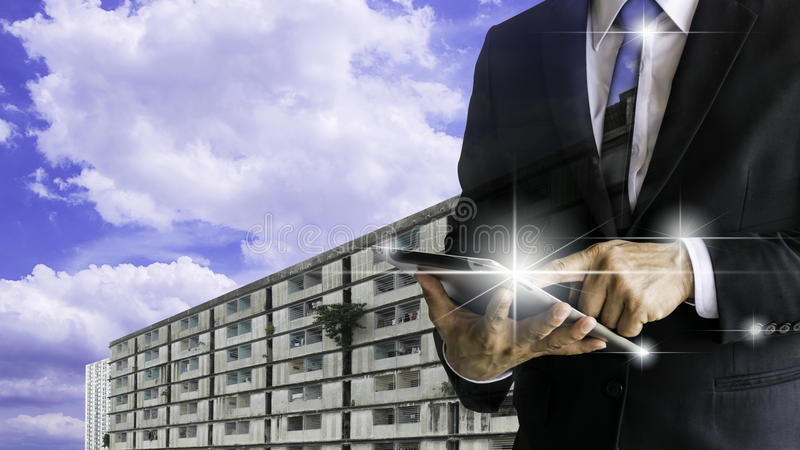 Officials are working on a tablet. Checking out a large industrial factory, wearing a black suit. White shirt, black tie royalty free stock photography