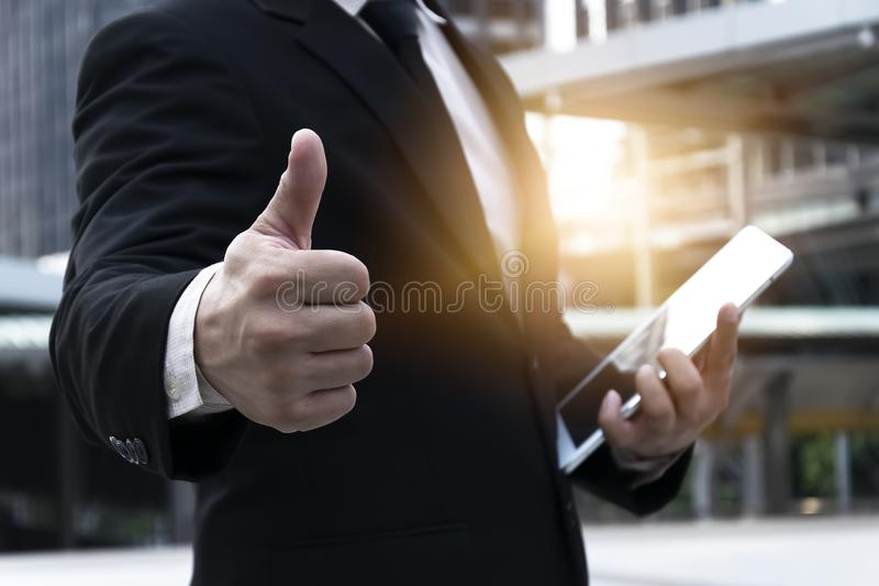 Officials are Thumbs up Thumbs up. Officials are working on a tablet,Construction plan to business,wearing a black suit,White shirt,Thumbs up Thumbs up And the royalty free stock images