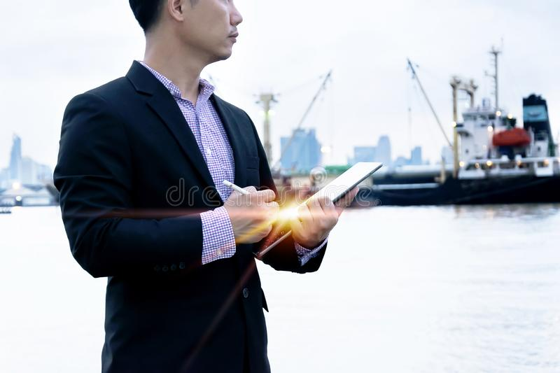 Officials are working on a tablet. Officials are working on a large industrial monitoring tablet, wearing a black suit and Plaid shirt,Commitment to work The aim royalty free stock images