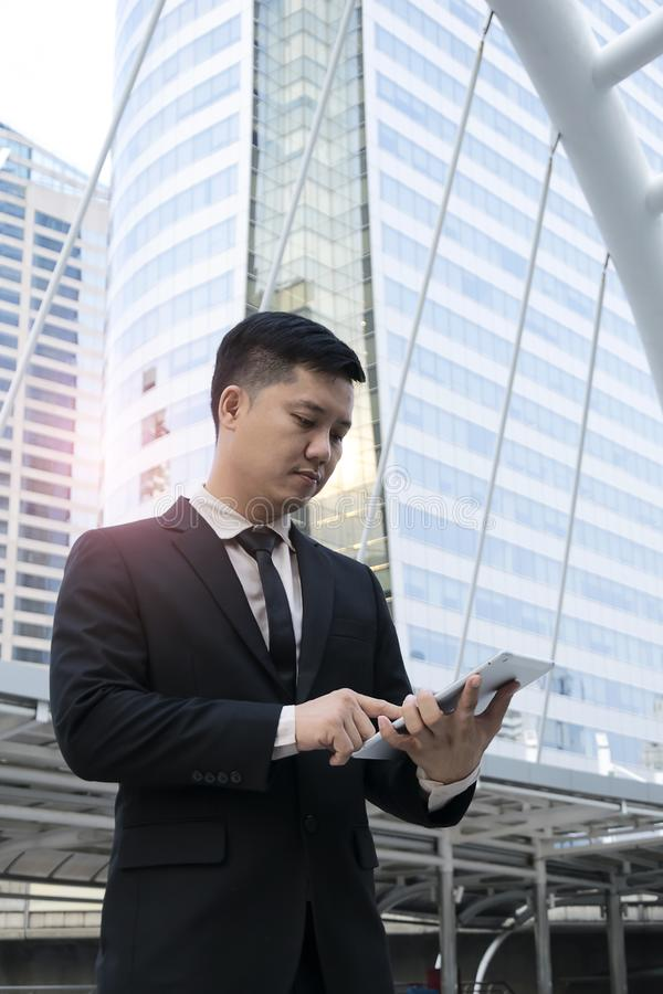 Officials are working on a tablet. Construction plan to business,wearing a black suit,White shirt,The path of capital`s prosperity,Real Estate Business stock image