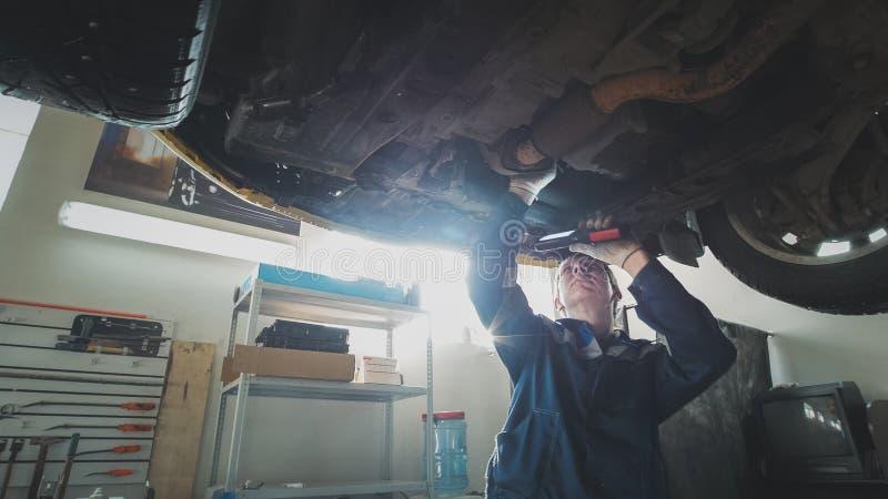 Officina automatica meccanica - un meccanico controlla la sospensione dell'automobile, grandangolare fotografie stock