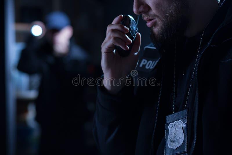 Offizier, der Funksprechgerät verwendet stockfotografie