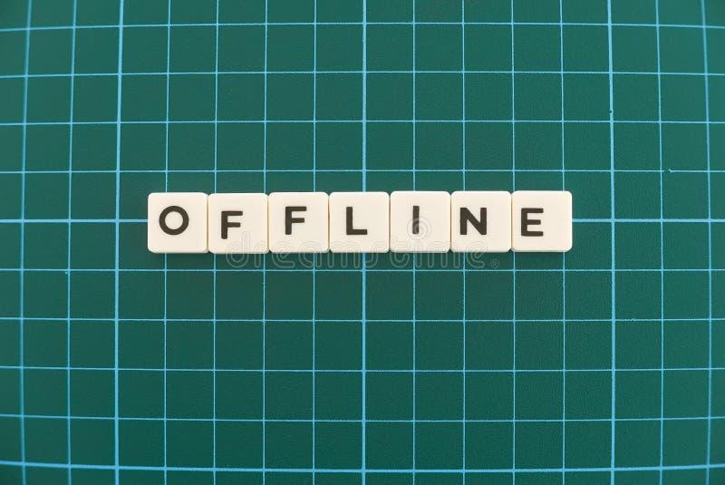 Offlinewort gemacht vom quadratischen Buchstabewort auf grünem quadratischem Mattenhintergrund lizenzfreie stockfotos