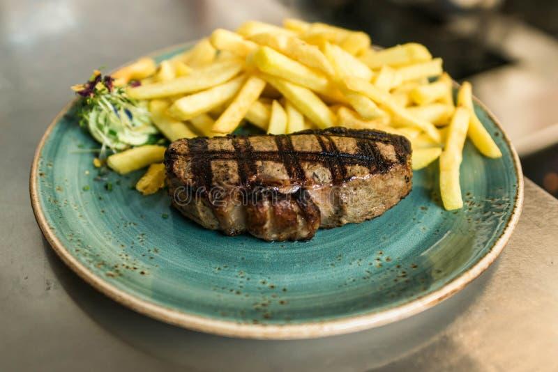 Offra la bistecca arrostita servita con le patate fritte dorate croccanti e l'insalata verde fresca dell'erba dal burro di erba o fotografie stock