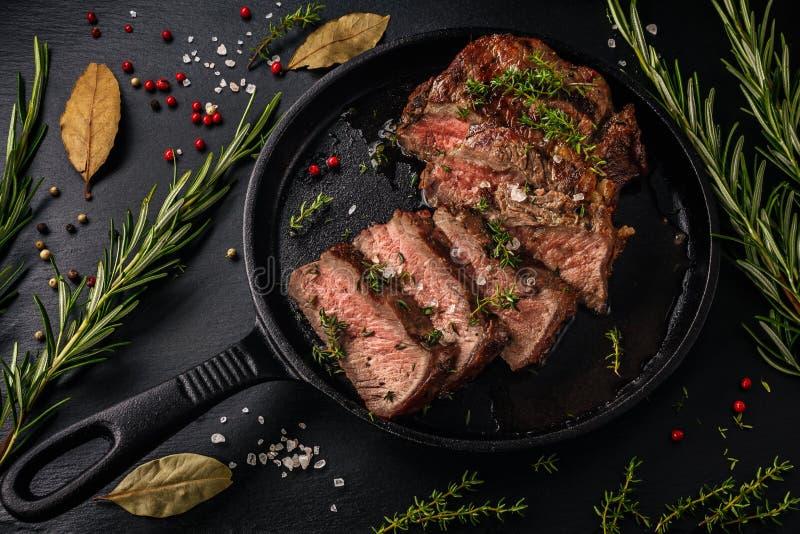 Offra la bistecca di manzo affettata di sous-vide dentro da una pentola del ghisa fotografia stock