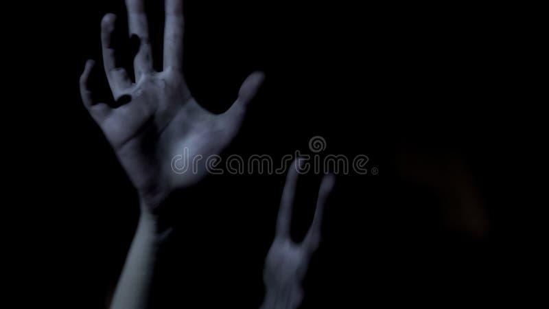Offret räcker sträckning ut i mörker som tigger för hjälp, läskig thriller royaltyfria foton