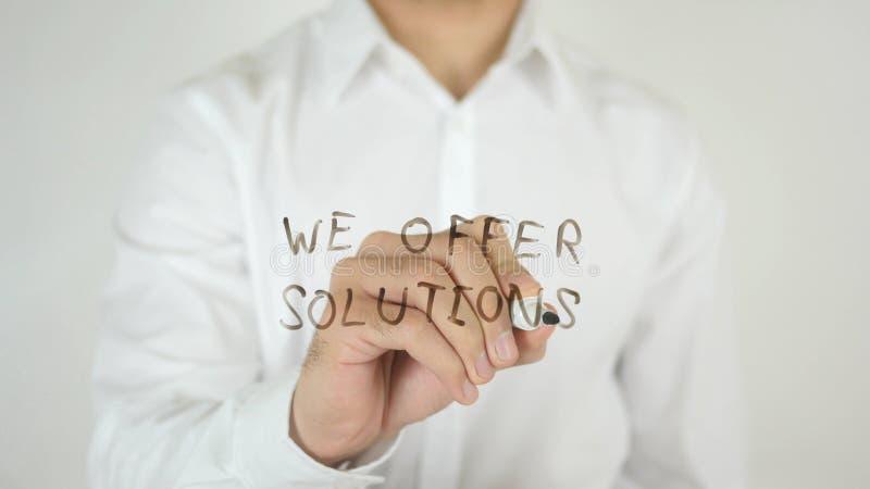 Offriamo le soluzioni, scritte su vetro fotografie stock