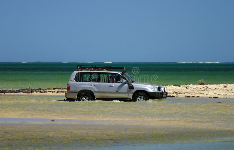 Offroad 4x4 vehicle on Beach. An offroad 4x4 travelling along a beachfront, with the ocean behind stock photo