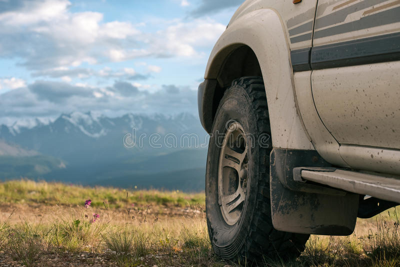 Offroad car concept with mountains. Wheel close-up. royalty free stock photos
