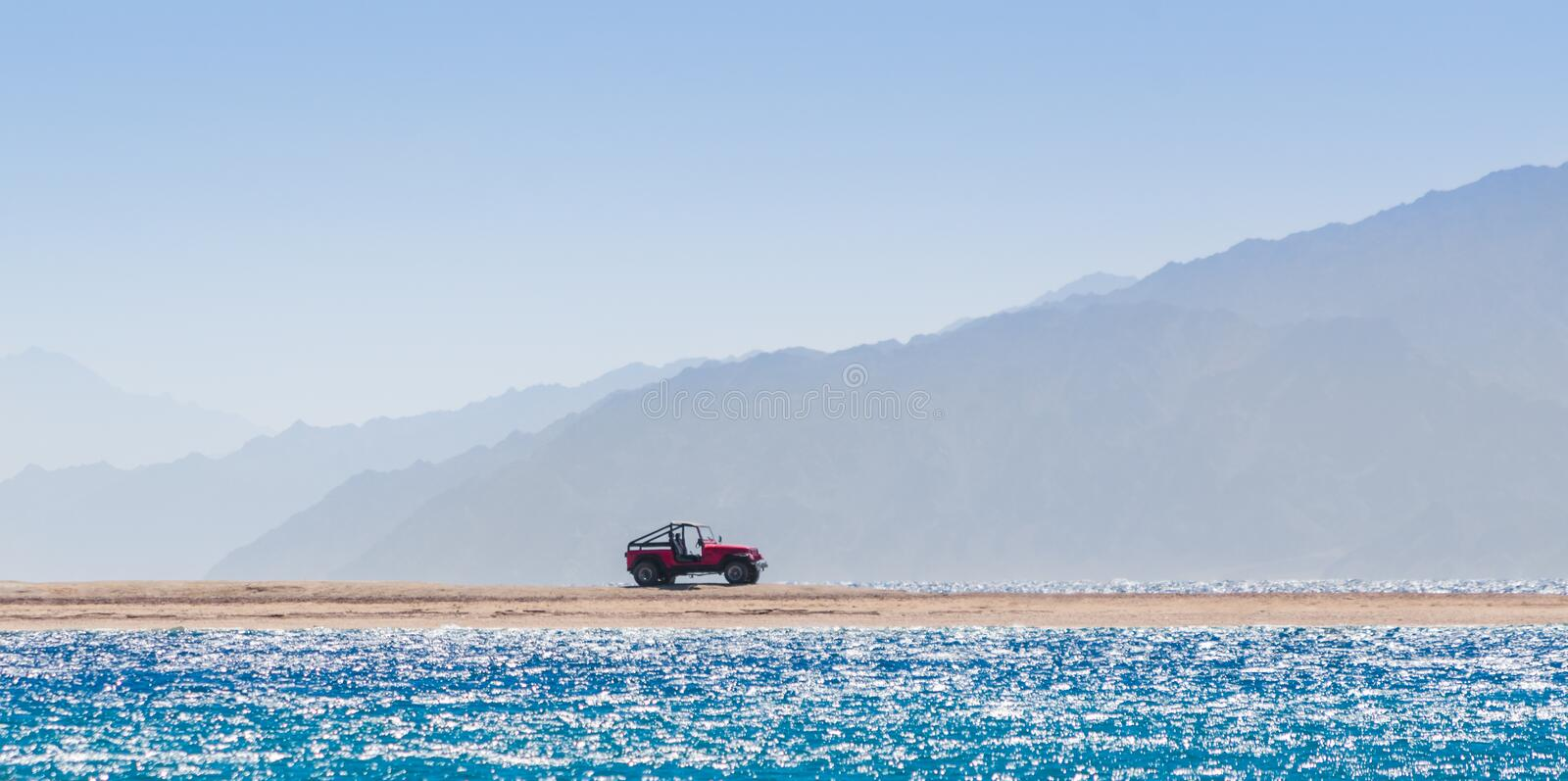 Offroad car on an island in the Red Sea against the backdrop of high cliffs in Egypt. Offroad car on an island in the Red Sea against the backdrop of the high stock photos