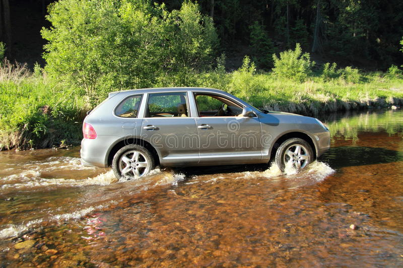 Offroad car in a river stock photos
