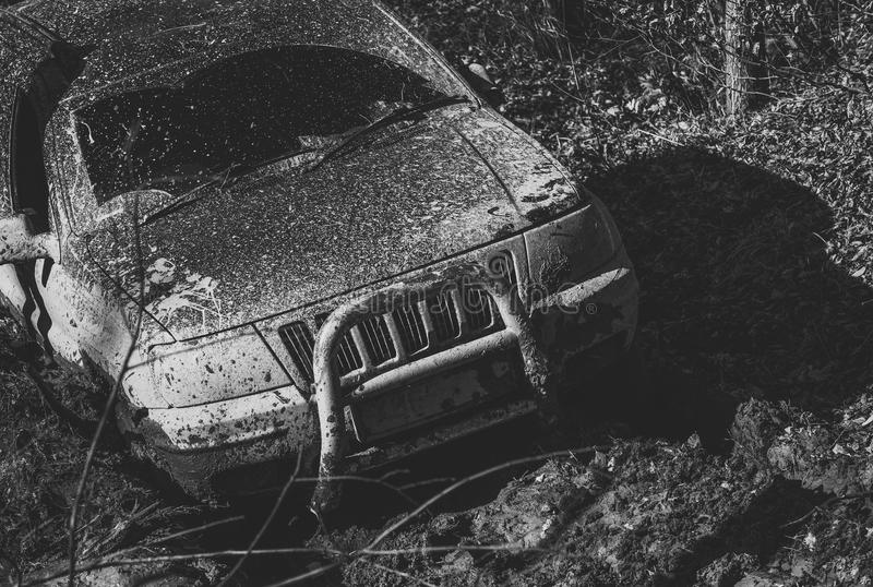 Offroad. Dirty offroad car with fall forest on background. SUV covered with mud on path with deep rut. Crossover driving through mud on sunny day. 4x4 racing stock photography