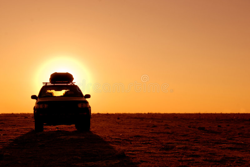 Offroad driving. Offroad 4x4 vehicle in the desert at sunrise royalty free stock photography