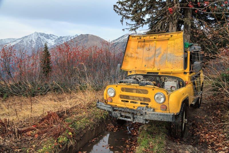 Offroad klibbade all terrängbil efter sammanbrott under reparation på bergskogvägen Scenisk liggande för höst arkivfoton