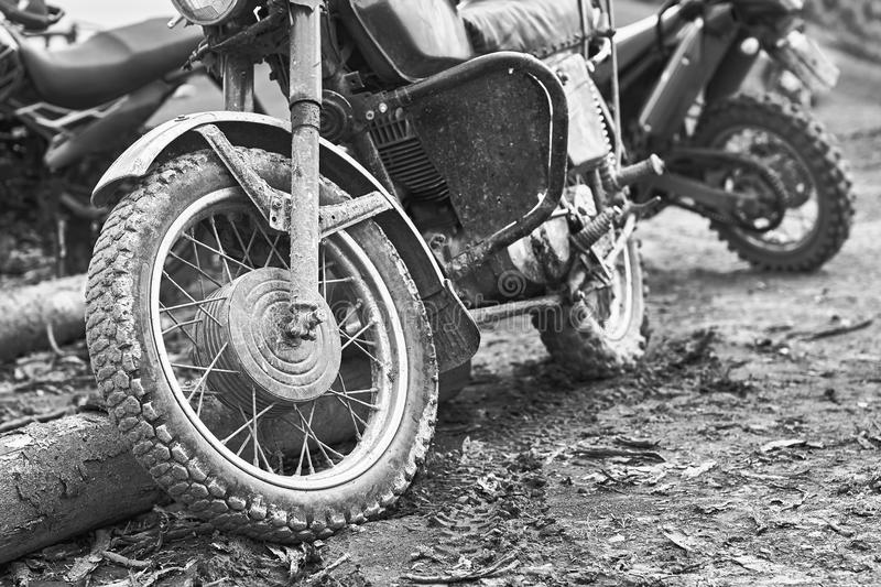 Offroad mountain motorcycle or bike taking part in motocros competition parked on dirty terrain road. Offroad mountain motorcycles or bikes taking part in stock images