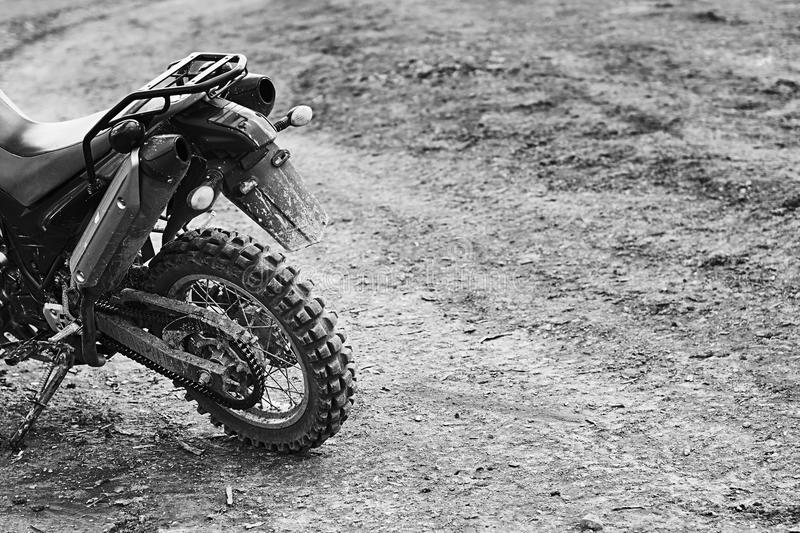 Offroad mountain motorcycle or bike taking part in motocros competition parked on dirty terrain road. Single offroad mountain motorcycle or bike taking part in stock image