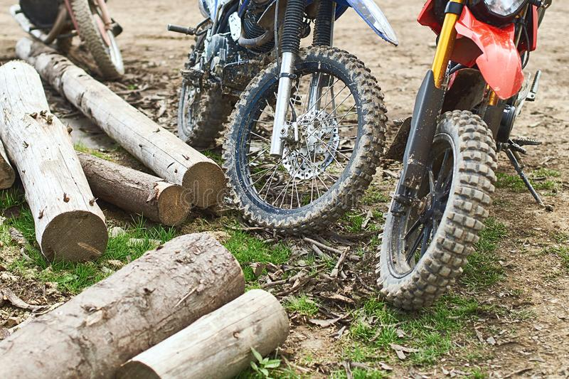 Offroad mountain motorcycles or bikes taking part in motocros competition parked on dirty terrain road. With wooden logs royalty free stock images
