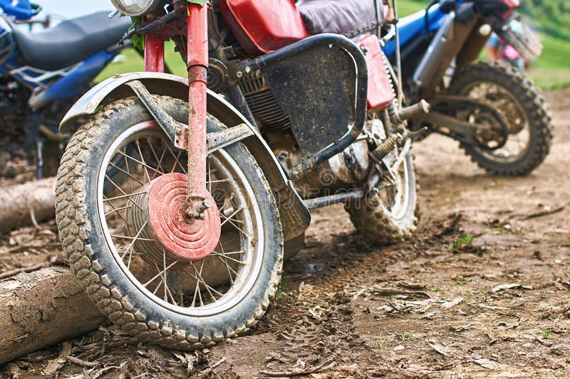 Offroad mountain motorcycles or bikes taking part in motocros competition parked on dirty terrain road. With wooden logs stock image
