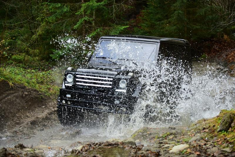 Offroad race in forest. Car racing with creek on way. Extreme driving, challenge and 4x4 vehicle concept. SUV or offroad. Car in black color crossing water stock photos