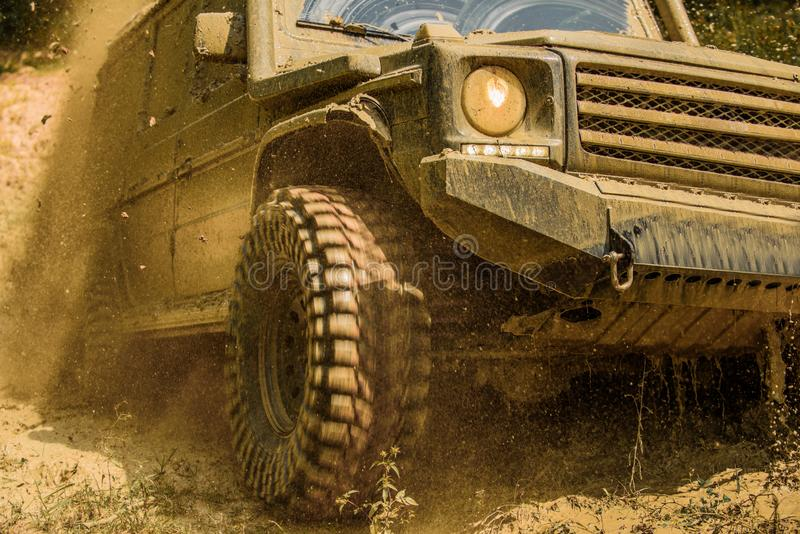 Offroad vehicle coming out of a mud hole hazard. Bottom view to big offroad car wheel on country road and mountains. Backdrop. Off-road travel on mountain road royalty free stock photography