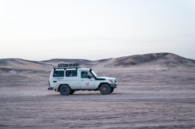 Offroad 4x4 vehicle driving in the desert, Hurghada, Egypt. Hurghada, Egypt - February 26, 2017: car, jeep or offroad 4x4 vehicle driving in desert on white sky stock photos