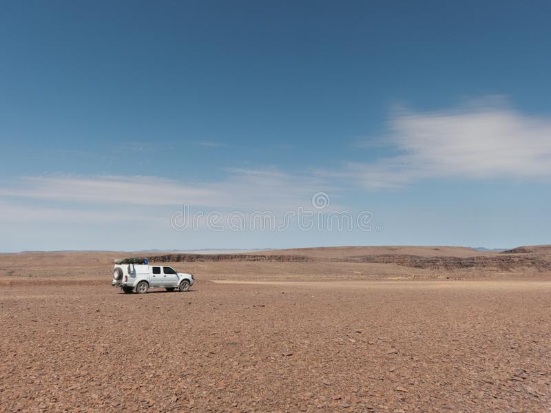 Offroad vehicle in stone desert. Offroad vehicle with rooftent in stone deset in the Ai-Ais Richtersveld Transfroniter Park in Namibia royalty free stock photos