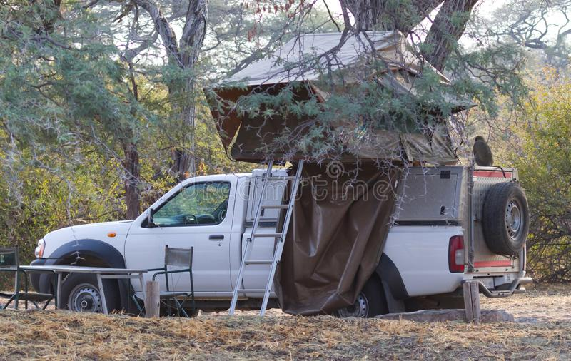 Offroad 4x4 vehicle with tent in the roof, monkey on the roof. Offroad 4x4 vehicle with tent in the roof ready for camping in the desert, monkey on the roof stock photo