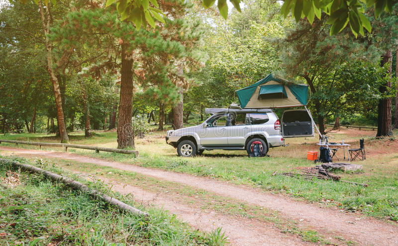Offroad 4x4 vehicle with tent in roof ready for. Landscape of 4x4 offroad vehicle with tent in the roof ready for camping next to dirt road with the forest in royalty free stock image