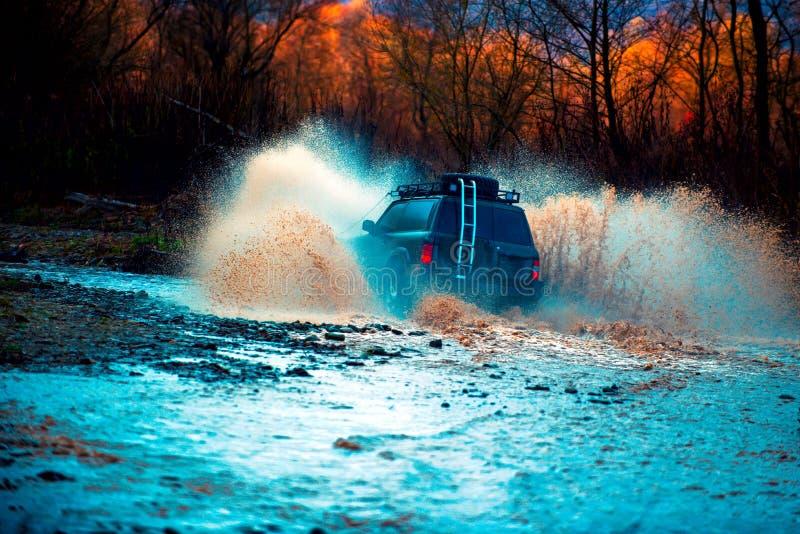 Offroading En bil under en tuff av-väg konkurrensdykning i en lerig pöl Extrema helger arkivfoton