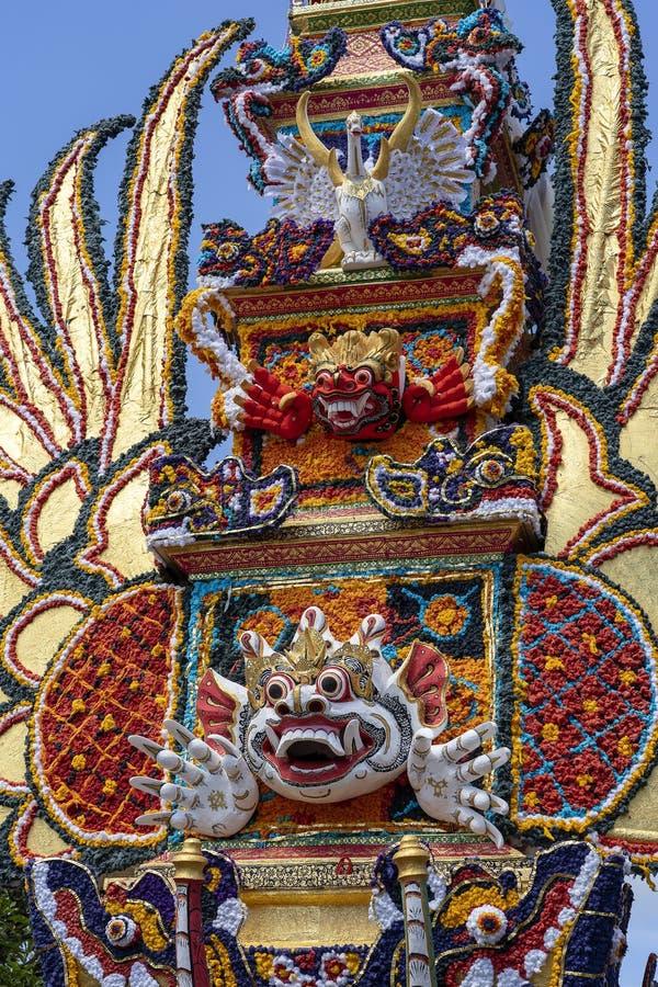 Offrono la torre di cremazione con le sculture tradizionali di balinese dei demoni e dei fiori sulla via centrale in Ubud, l'isol fotografia stock libera da diritti