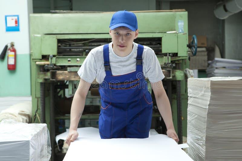 Offset- papper för materiel Man som arbetar i tryckfabrik royaltyfria bilder