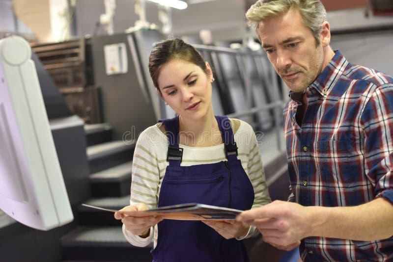 Offsetdrucker und Lehrling in der Druckindustrie lizenzfreie stockbilder