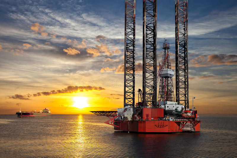 Offshore area at sunset. Oil platform and tanker ship on offshore area at sunset stock images