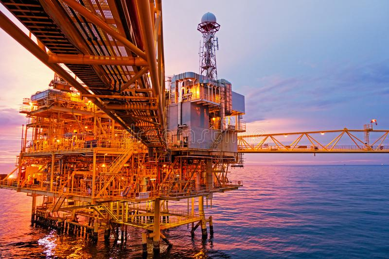 Offshore construction platform for exororation and production oil. And gas with bridge in evening time for power energy of the wolrd concept royalty free stock images