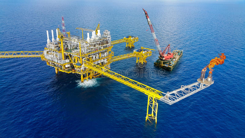 Offshore construction platform for production oil and gas, Oil and gas industry and hard work,Production platform and operation. Process by manual and auto stock images