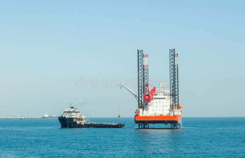 Offshore jack-up barge and supply vessel stock photography