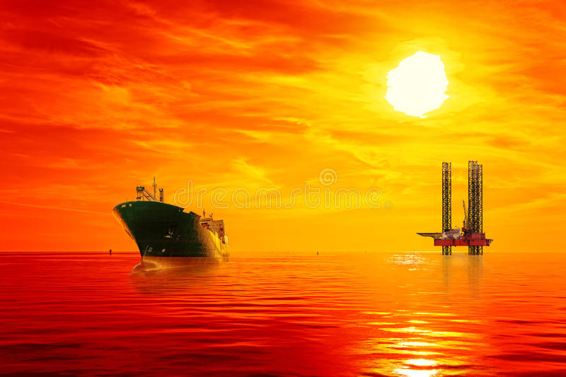 Offshore oil area at sunrise. Oil rig and tanker ship on offshore area stock image