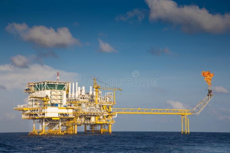 Offshore oil and gas central processing platform and flare platform while flaring waste gases. Offshore oil and gas central processing platform and flare stock image