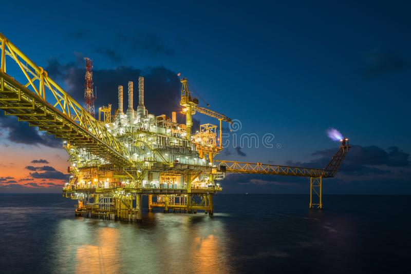 Offshore oil and gas central processing platform in sun set where produced raw gases and treat then sent to onshore refinery. royalty free stock images